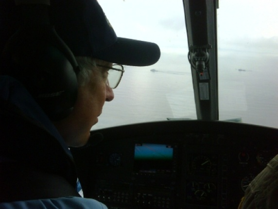 Secretary Salazar surveys oil on the water from the flydeck of a Coast Guard HC-144A Ocean Sentry.
