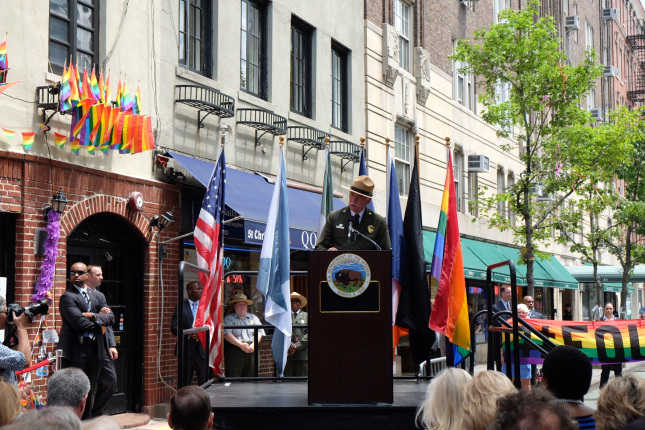 Director Jarvis speaks to a crowd at the ceremony while standing behind a wooden podium