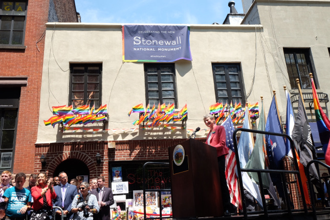 Secretary Jewell addresses a crowd while standing behind a wooden podium and in front of a chorus of rainbow flags.