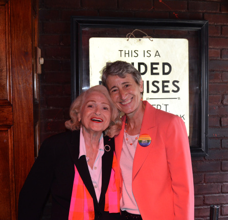 "Secretary Jewell smiles brightly while posing for a photo with Edie Windsor. Jewell is wearing a coral blazer with a ""Stonewall 2016"" pin, and Windsor is wearing a black coat with a pinkish red scarf wrapped around her neck."