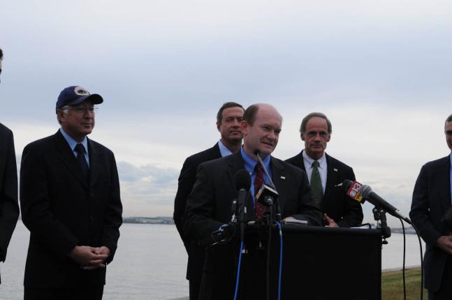 Senator Chris Coons speaking at the podium.