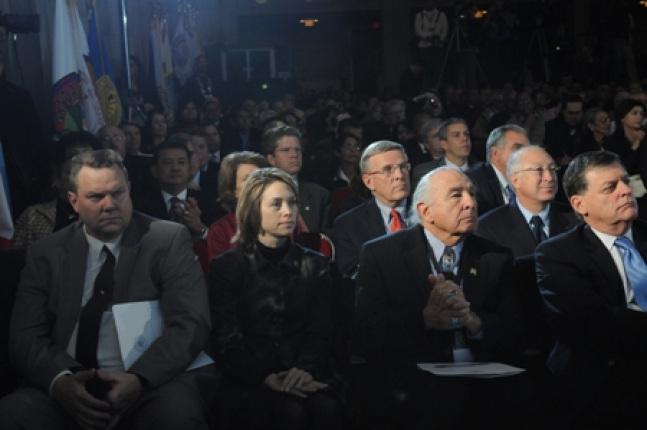 Administrators listen as the president speaks.