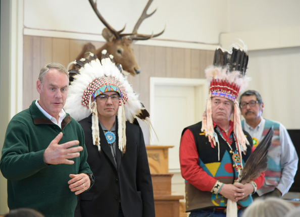 Four men in room, one is Secretary Zinke, three look on while two wear headresses