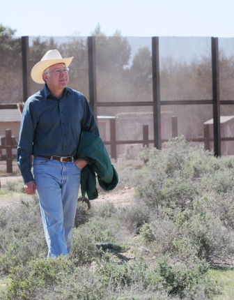 Secretary of the Interior Ken Salazar walks along border fence at Organ Pipe Cactus National Monument.