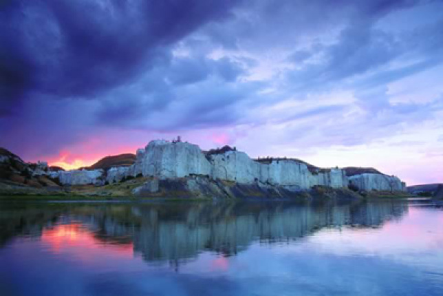 The sun, sky, and cliffs — and their reflection in the Upper Missouri River.