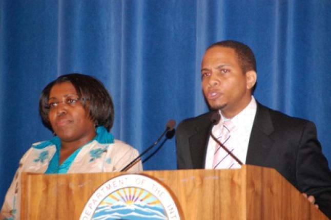 OPM's Quewetta Fernando and Roland Edwards speaking at podium.
