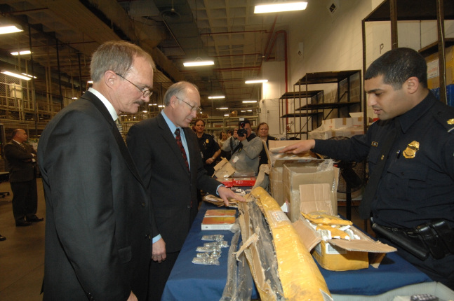 DHS Officer John Saleh displays counterfeit items that have been confiscated at the port. Left to right are FWS Director Hamilton, Secretary Salazar and Officer Saleh.