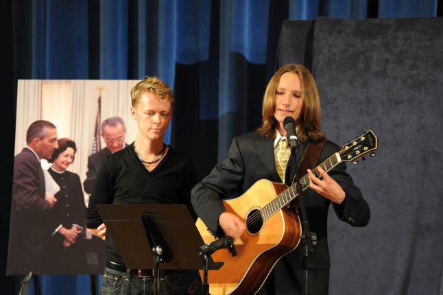 "Denis and Jonah Udall on stage as Jonah performs ""Where the Mountains Meet the Sea,""written by Denis Udall"