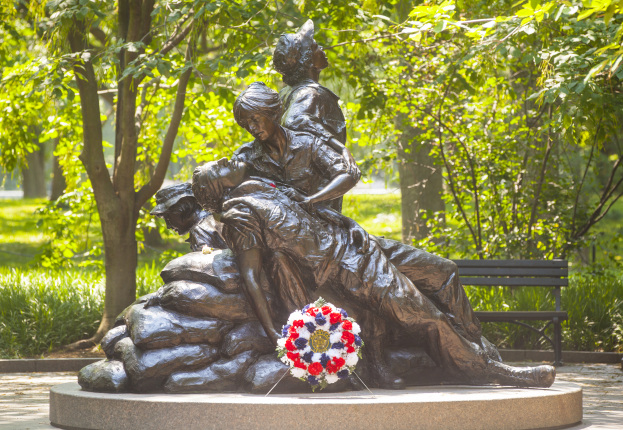 Brown statue of one woman sitting on a rock as a man lays in her arms, another woman looks towards the sky, and a final woman looks at the ground. Green trees are behind the statue and a red, white, and blue wreath sits in front of it.
