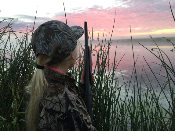 A young girl with blonde hair wears camouflage hunting clothes and holds a shotgun while standing in tall grass and looking at a pink sunrise.