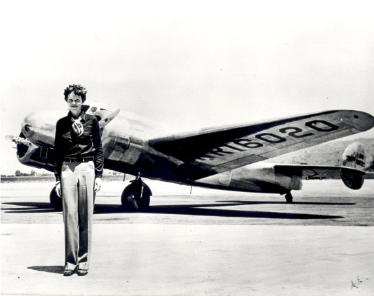 Black and white photo of a woman in pants and a light jacket standing in front of a small plane facing the camera.