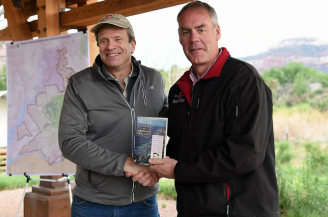 Secretary Zinke stands next to a man, shaking his hand and holding a paperback book, under a shelter with a map in the background