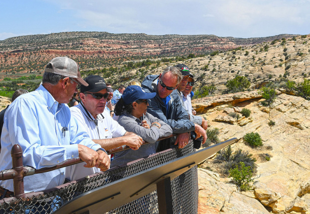 Secretary Zinke with a group of men and women leans against the railing under the bright sun overlooking the craggy landscape