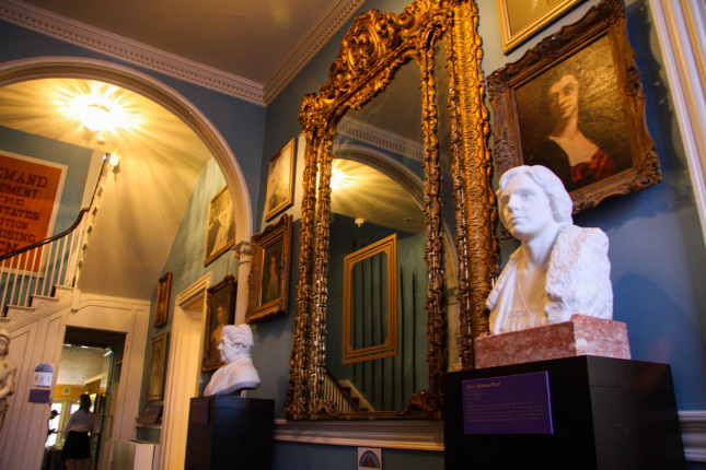 A room with blue painted walls, a white staircase, two white busts resting on marble pedestals, and many gold framed photos lining the wall. There is a large gold framed mirror that rests in the middle of the wall.