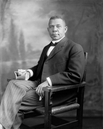 A historic black and white photo of a distinguished looking African American man in a suit sits in a wooden chair.
