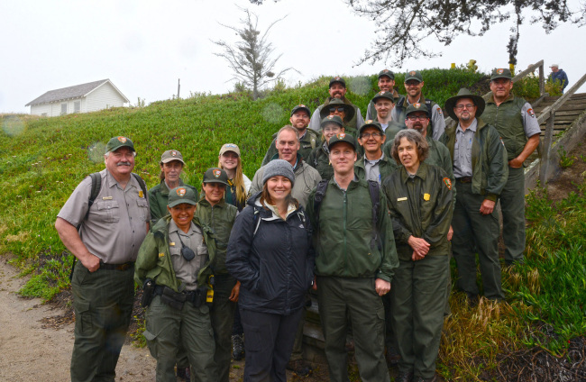 Secretary Zinke stands on a slope of green grass with a large group of men and women in National Parks' uniforms