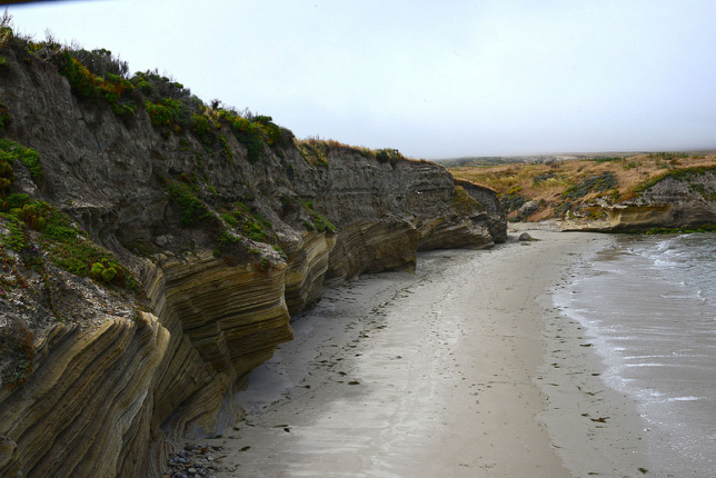 Water washes upon the beach leading to bluffs on a cloudy day