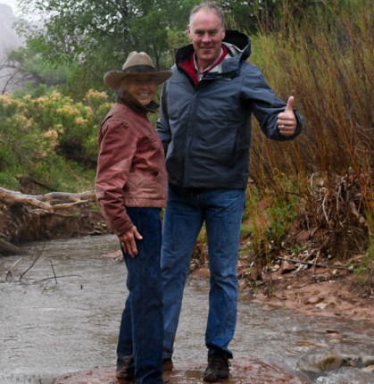 Secretary Zinke gives the thumbs standing next to a woman in a brown jacket on an earthen bank in the midst of a flowing river