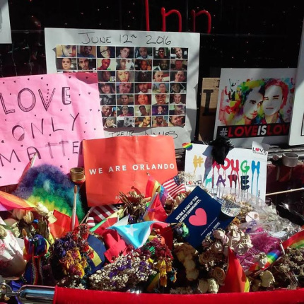 Flowers, flags, photos, and posters remembering the victims of the 2016 Orlando Pulse nightclub shooting adorn the front of the Stonewall Inn.