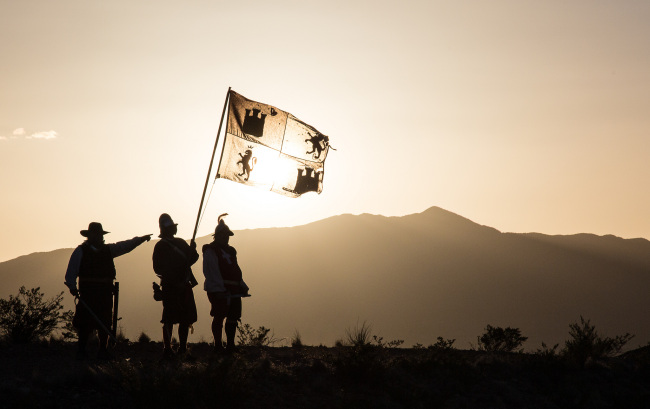 Three men dressed as Spanish explorers wave a flag as they stand on a hillside in bright sunlight.