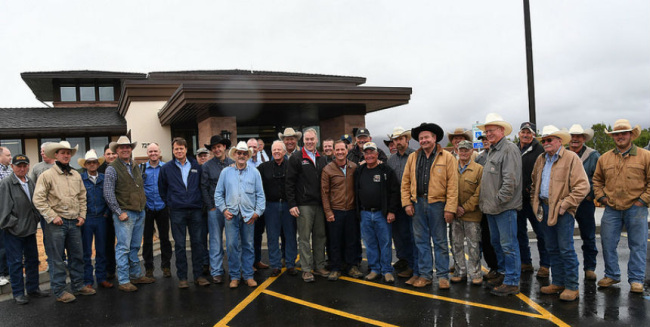 A large group of men, many with cowboy hats stand in a parking lot outside a small building