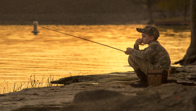 A young boy kneels on a riverbank with a fishing pole at sunset.