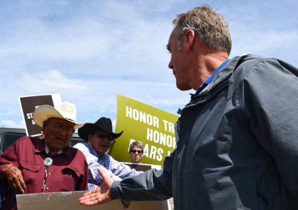 Secretary Zinke extends his arm to shake hands with a man a cowboy hat behind a brown sign
