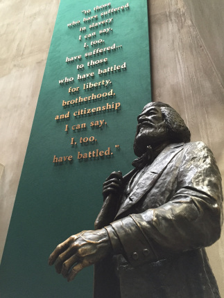 A statue of Frederick Douglass standing next to a sign in a visitor center.