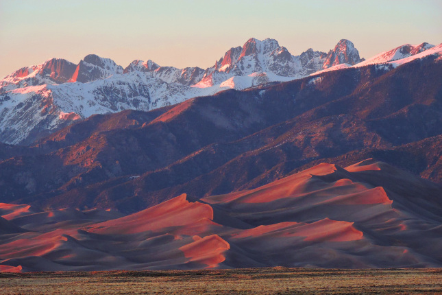 Tall sand dunes and mountains glow in the red light of sunset.