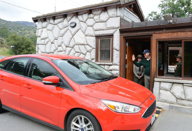 A red car stops next to a stone gatehouse with Secretary Zinke inside the post