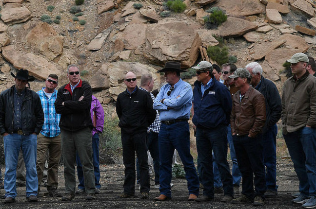 Secretary Zinke stands at the base of a rocky slope on a dirt trail with a group of persons