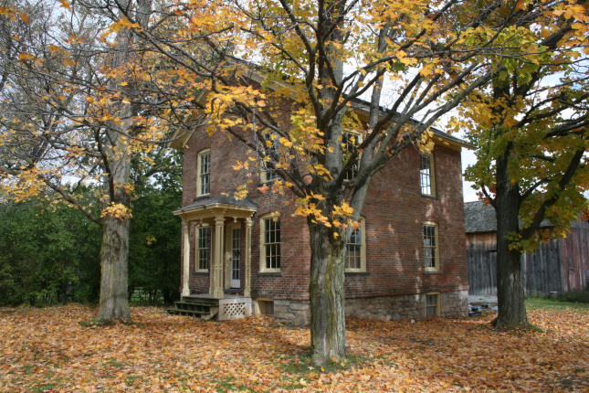 Photo of a small brick house with a porch surrounded by trees showing their autumn colors.