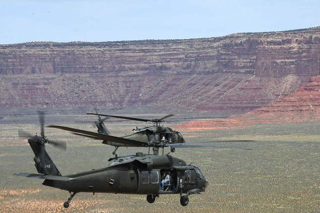 Two large helicopters fly over a vast arid landscape, with a plateau in the distance