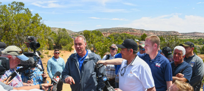 Secretary Zinke speaks to the assembled reporters and cameramen with the dry backdrop of arid land