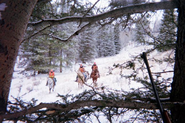 Three people wearing hunting gear ride horses through a snowy forest.