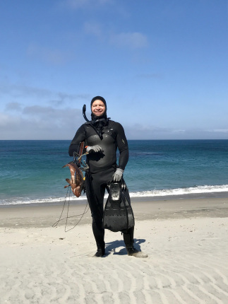 A man in a wetsuit stands on a beach holding a spear gun and several large fish.