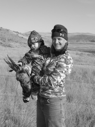 A woman in hunting gear holds a toddler in her arms who is holding a dead bird.