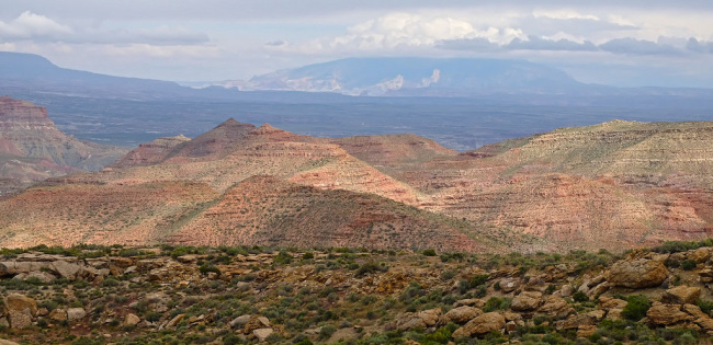 Ridges with scrub brush and small mountains and plateaus in the distance