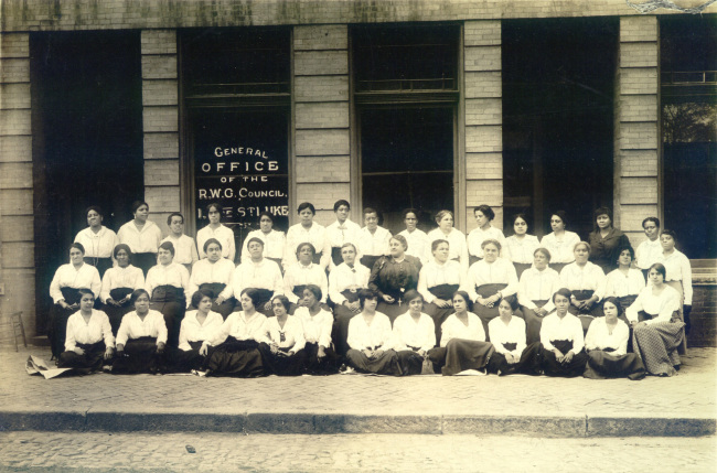 A historic black and white photo of a group of about 50 African American women posing in front of a brick building with large windows.