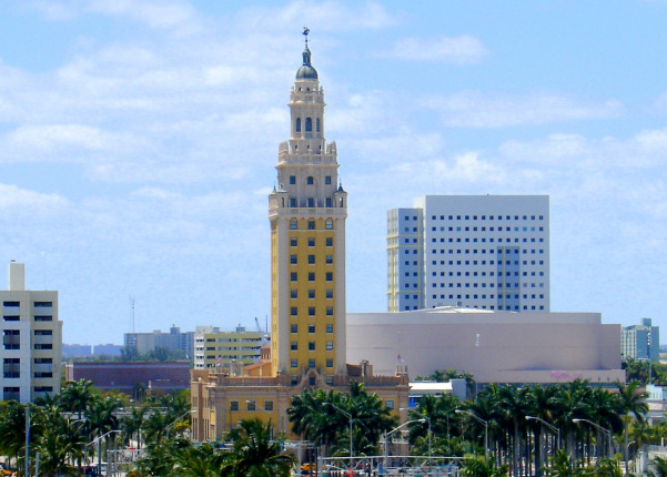 A tall yellow building with an ornate pointed roof stands among the Miami skyline.