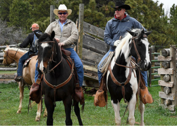 Secretary Zinke on a horse wearing a cowboy hat and sunglasses next to a man dressed likewise with an old wooden fence in the background