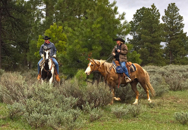 Secretary Zinke on horseback pauses in the brush with another person on a horse beside him