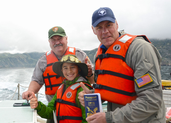 Secretary Zinke in a baseball cap holds a blue book, next to a boy wearing a wide-brimmed bat with gold pins, and a man also in a baseball cap; all three wear orange life preservers