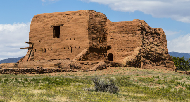 The tall walls of an old brown adobe brick building stand on a grassy hill.