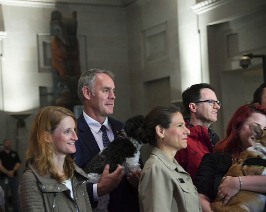 Secretary Zinke and other men and women with dogss are filmed