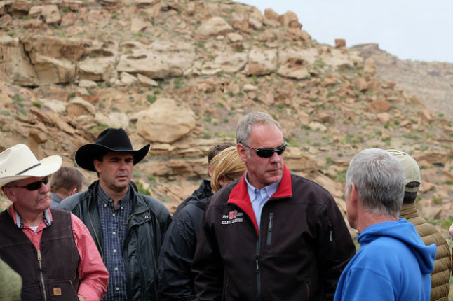 Secretary Zinke stands near rocky slopes listening to a group of persons next to him