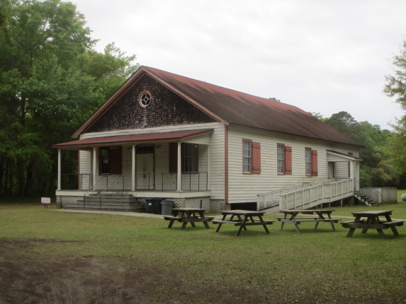 Photo of a long, one story wooden hall with a wide porch and picnic tables on the front lawn.