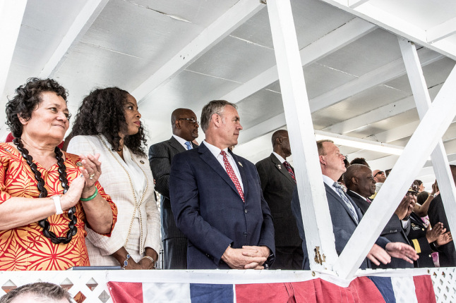 Secretary Zinke stands with many guests in a wooden, open-air structure painted white