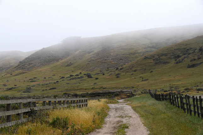 Hills covered with fog overlook an open dirt road with a wooden fence on the sides