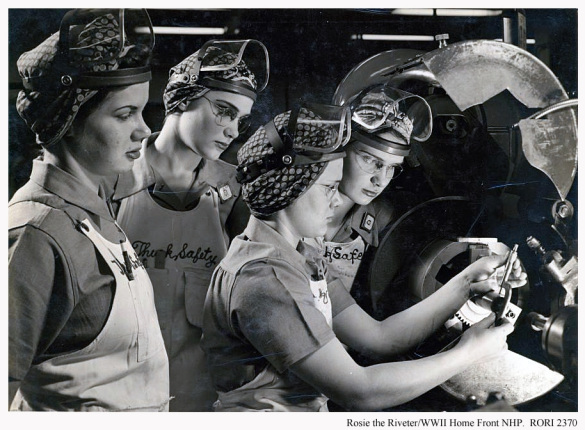 A black and white photo of four women wearing aprons, protective eye masks on their heads, and bandanas covering their hair, observe a metal machine.